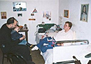 Отец Лука с одним из своих детей посещает больную в больнице Тираны
