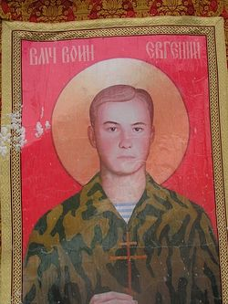An icon of Martyr Evgeny Rodionov on a banner.