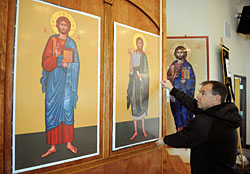 Council president Nicolae Toderica gets ready to frame the icons of Jesus Christ, left, and St. John the Baptist on Wednesday at St. Dimitrie the New Romanian Orthodox Mission Church in Frederick. Photo by Lewis Geyer, Times-Call.