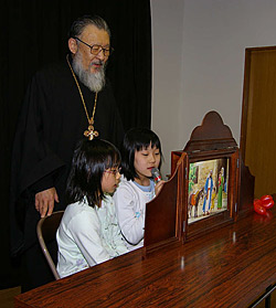 "Rector of the church in Sapporo Archpriest Alexis Matsudaira is helping Alexandra Yamaguti and Rebecca Sato show ""holy pictures""."