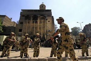 Egyptian Army soldiers stand guard outside the burned Virgin Mary church in the Imbaba neighborhood of Cairo, Egypt AP