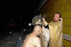 Отец Артемий совершает Таинство Крещения