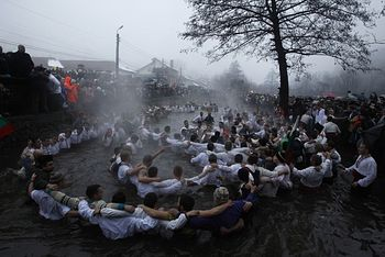 Загрузить увеличенное изображение. 950 x 634 px. Размер файла 161718 b.  Bulgarian men dance in the icy waters. Photo:Reuters.