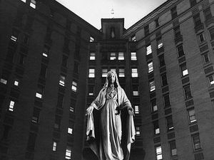 A statue of the Virgin Mary in front of a Catholic hospital.