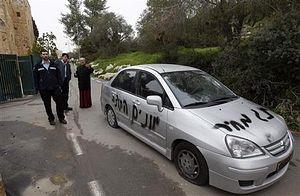 Офицеры полиции Израиля и священник осматривают машину, на которой на иврите написано