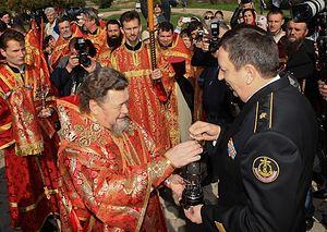 Контр-адмирал Александр Федотенков передает Благодатный огонь митрополиту Симферопольскому и Крымскому Лазарю