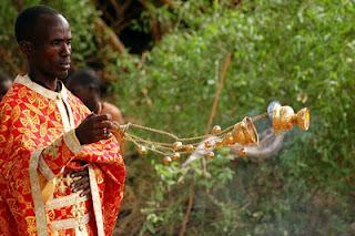 Kenyan priest censing the faithful.