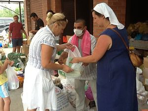 """A Moslem who """"simply witnessed the Christian compassion"""" desires Baptism. Sister of Mercy Irina Sechina hands out humanitarian aid."""