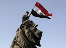 A demonstrator carries an Egyptian flag near Tahrir square as demonstrators gather to mark the first anniversary of Egypt's uprising, January 25, 2012.