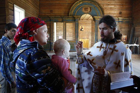 Отец ириней совершает крещение в сельском храме. Фото: Иван Кудласевич
