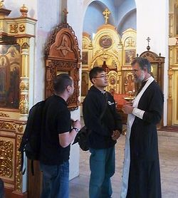 A priest discusses the faith with Tokashi Kishi before his baptism.