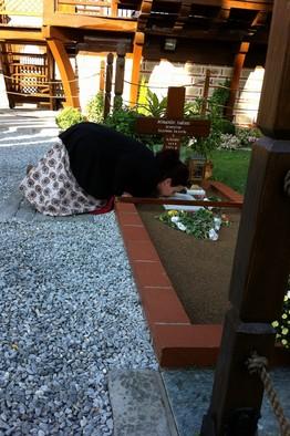 A woman praying at the Elder's grave in Souroti. Photo: Gordon Fairclough/The Wall Street Journal.