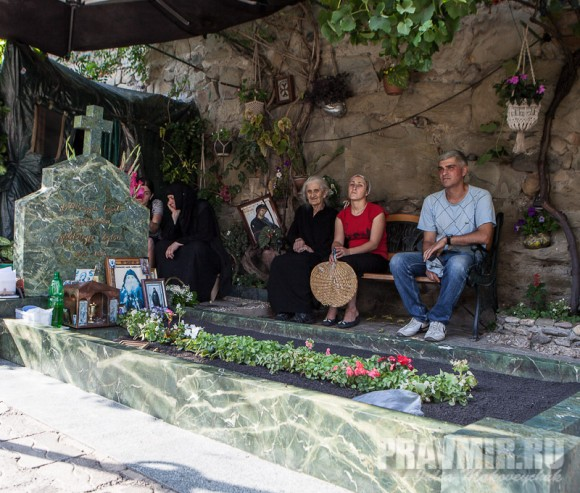Люди, сидящие у могилы. Фото Юлии Маковейчук.