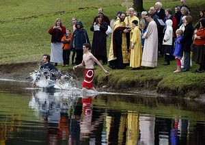 Ryan Haydoc, 28 (left), and Ben Weatherhogge, 15, enter Blackman's Lake in Snohomish to retrieve a cross thrown by Father David Sommer of St. Thomas Orthodox Church. The congregation gathered at the lake to celebrate the Feast of Theophany, which commemorates the baptism of Jesus.