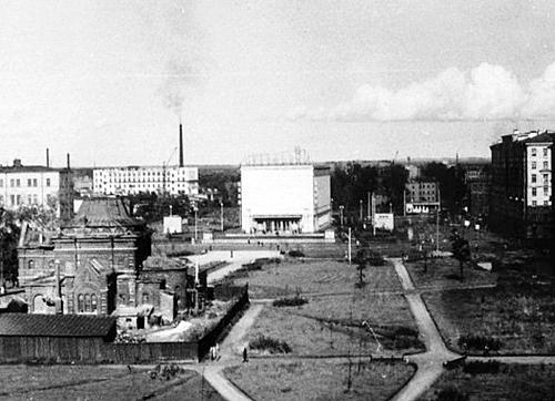 Коробка без окон на дальнем плане — кинотеатр «Спутник», построенный в 1955-1965 годах. Часть кладбища сровняли с землей и водрузили кинотеатр прямо поверх могил. Церковь уже обнесена забором, кресты сняты и купол частично разобран