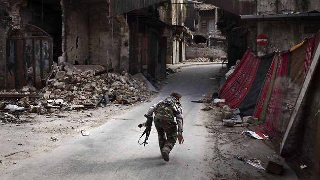 A Syrian rebel crosses a street while trying to dodge sniper fire in the old city of Aleppo in northern Syria on March 11. Picture: AFP