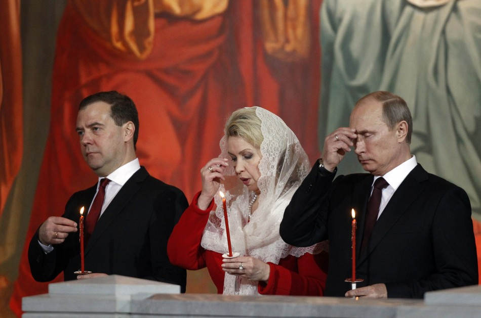 Russian President Vladimir Putin (R), Prime Minister Dmitry Medvedev (L) and his wife Svetlana (C) attend an Orthodox Easter service conducted by the Patriarch of Moscow and All Russia Kirill in the Christ the Saviour Cathedral in Moscow May 5, 2013. Photo: Reuters