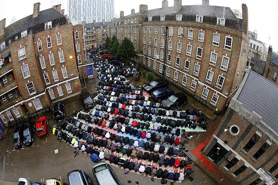 Muslims attend Friday prayers on a rainy first day of Ramadan, at the courtyard of a housing estate next to a small BBC community centre and mosque in east London (Reuters/Chris Helgren)
