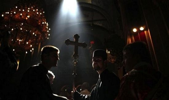 A Greek Orthodox altar boy holds up a ceremonial cross as a ray of light enters the Church of the Holy Sepulchre in Jerusalem's Old City in April 2012