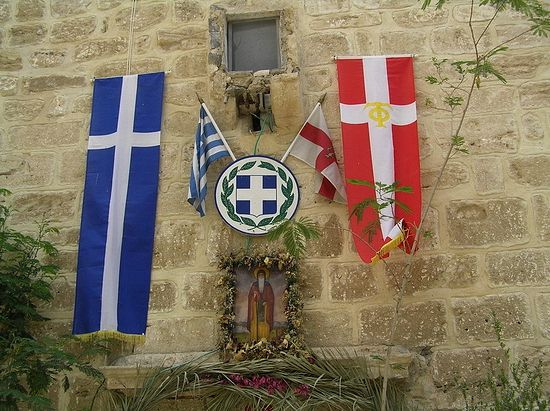 The flags of Greece and of the Guardians of the Holy Sepulchre, hanging above the monastery entrance.