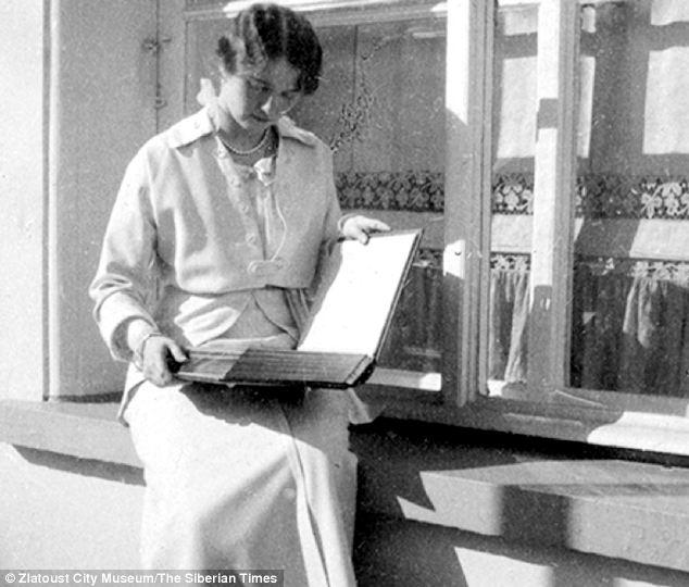 Grand Duchess Olga is seen looking through a family album.
