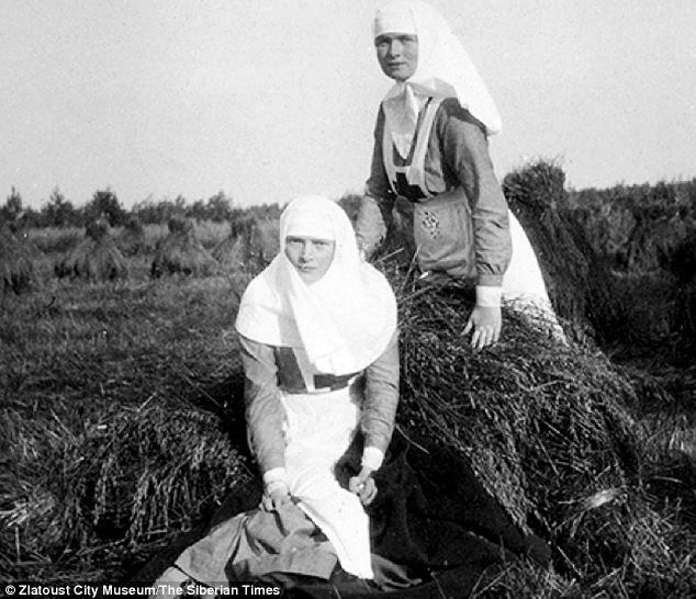 The grand duchesses Olga and Tatiana as sisters of mercy, at the hay-cutting. Pprivate family photo taken in 1916..