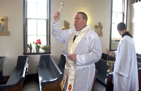 Father James Hamrick sprinkles holy water as he walks amid the pews at St. John the Baptist Orthodox Church. David Frey photo.