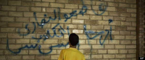 "A supporter of ousted Egyptian President Mohammed Morsi paints graffiti on the wall of a Coptic Church in Assiut, Upper Egypt, Tuesday, Aug. 6, 2013.Arabic graffiti reads, ""Boycott the Christian dogs."""