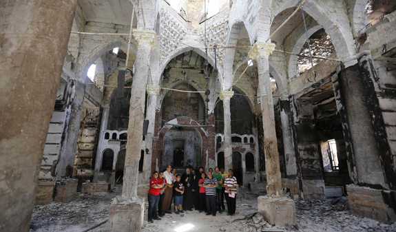 A Coptic Orthodox bishop prays with local residents at burnt and damaged evangelical church in Minya, Egypt, Aug. 26. (CNS photo/Louafi Larbi, Reuters)