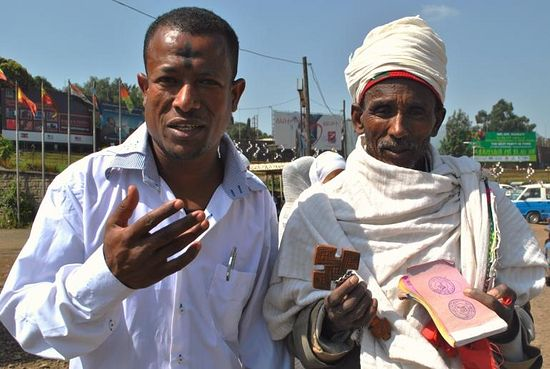 Johannes, 34, who wears the mark of the cross on his forehead to celebrate the holiday Meskel, stands with an Ethiopian Orthodox Christian clergyman. Photo: IBTimes/Jacey Fortin