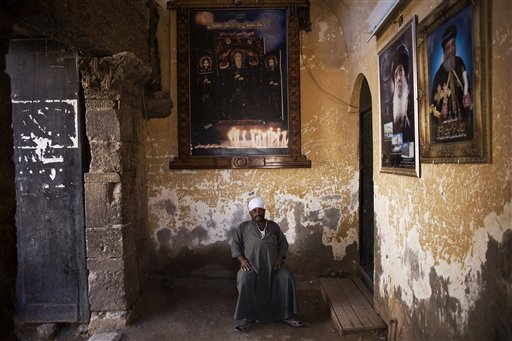 An Egyptian man guards the gate of a church at the Red Monastery in Sohag