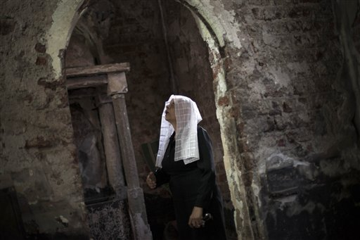 An Egyptian Coptic woman prays at a church burnt by radical Islamists on Aug. 14 in the town of Abanoub