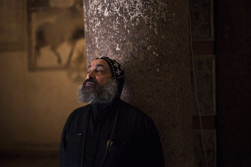 Father Antonius stands in the Anba Bishay Church while looking at the paintings the Anba Bishay Church at the Red Monastery