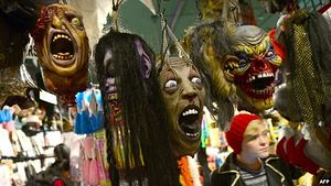 Halloween masks hang in a shop window in New York City