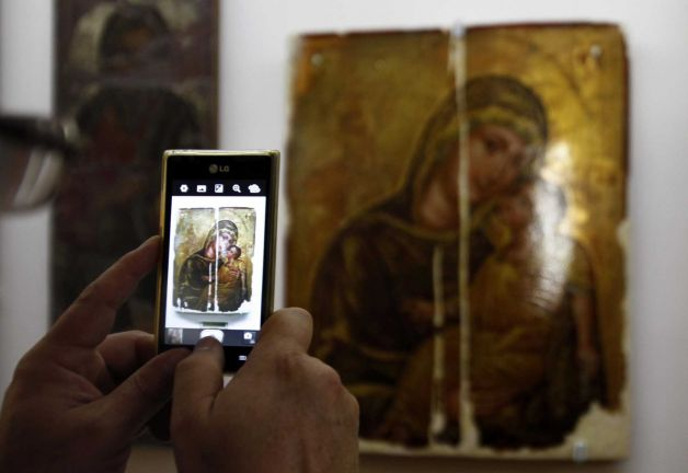 A man use his mobile to take a photo of the 14th century icon of the Virgin Mary, or Panayia, the Merciful after returned looted icons at the Byzantine Museum in capital Nicosia, Cyprus. Photo: Petros Karadjias, AP / AP