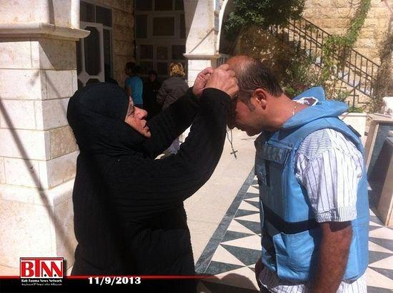 После освобождения Маалюли от боевиков в сентябре 2013 г; Монахиня одевает крест сирийскому журналисту