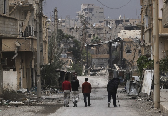 Free Syrian Army fighters walk along a street in Deir al-Zor that has been scarred by war. Photo: Khalil Ashawi/Reuters