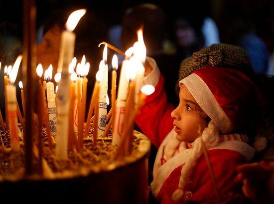Палестинская девочка зажигает свечу в храме Рождества Христова в Вифлееме. 06/01/2014.