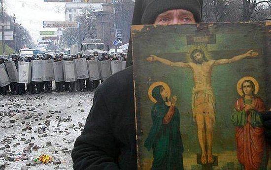 Монах с иконой стоит между митингующими и «Беркутом»