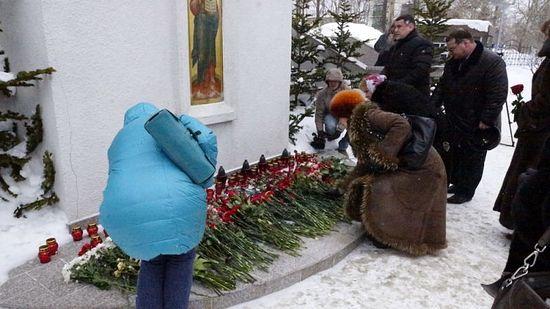 Люди кладут цветы у стены кафедрального собора Южно-Сахалинска
