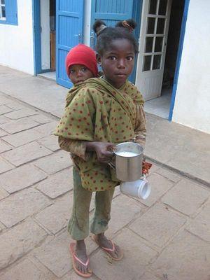 Маленькая девочка с кружкой молока и братишкой