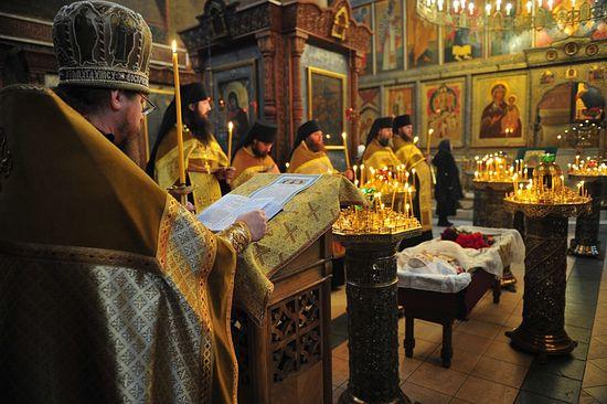 Архимандрит Тихон читает разрешительную молитву над усопшей Евгенией Матвеевной Грикой. Фото: Православие.Ru