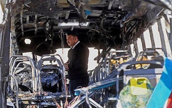 Полицейский во взорванном автобусе. Фото AFP