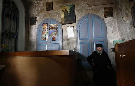 A Greek orthodox priest guards a chapel built inside the Orthodox Christian monastery of the Temptation near the West Bank city of Jericho, on February 22, 2014. (Photo: AFP- Thomas Coex)