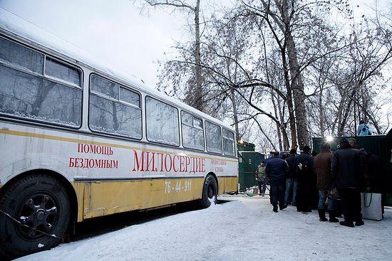 Бездомные ожидают своей очереди на вход на территорию социального пункта. Слева – автобус православной службы «Милосердие»