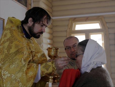 Отец Михаил причащает Эльзу Семёновну
