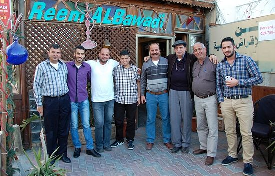 "​The many Georges of the Talgieh family standing outside the ""Abu George"" coffee shop"