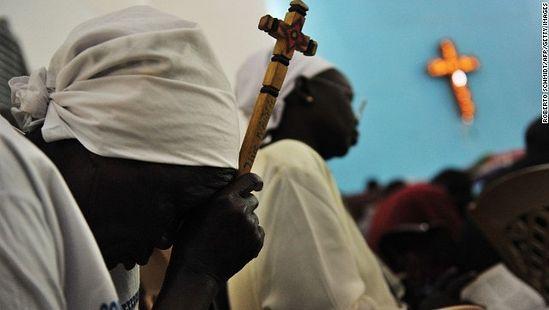 Суданская женщина молится. Фото CNN