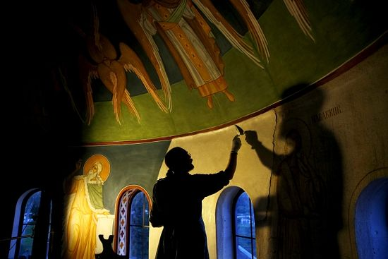 Just before dawn, Father Moses Fredricks smooths plaster in preparation for the fresco painting of the Prophet Joel on the dome at St. Seraphim of Sarov Orthodox Church.