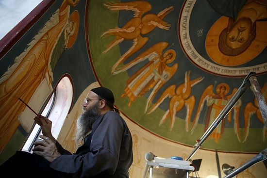 Father Patrick Doolan adds the finishing touches to a fresco painting of the Prophet Elias.
